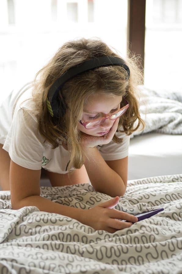 使用在她的手机的女孩在床上 免版税库存照片