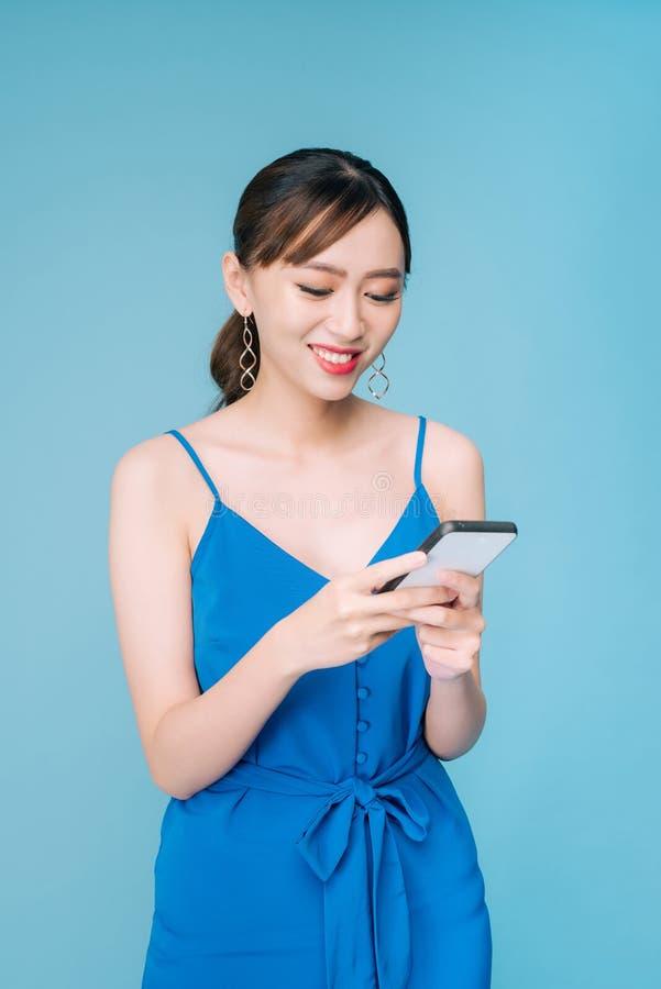 使用在她的携带式装置的可爱的妇女正文消息特点在演播室 图库摄影
