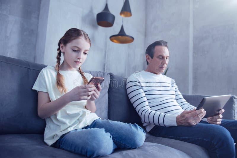 使用在她的智能手机的宜人的女孩 免版税库存图片
