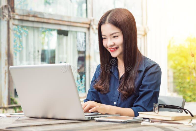 使用在她的膝上型计算机c的微笑的年轻愉快的亚裔妇女技术 免版税库存照片