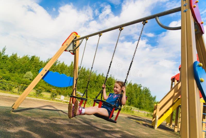 使用在室外操场的孩子在雨中 孩子在学校或幼儿园围场使用 在五颜六色的摇摆的活跃孩子 ?? 免版税图库摄影