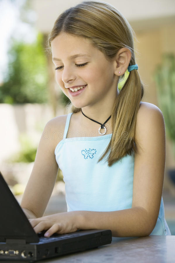 使用在室外露台的女孩膝上型计算机 免版税库存图片