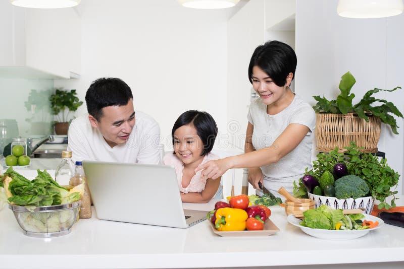 使用在家一起计算机的年轻亚洲家庭 免版税库存图片