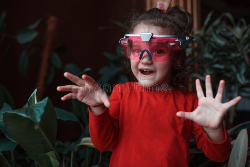 使用在家与VR耳机玩具的愉快的小孩女孩 库存图片