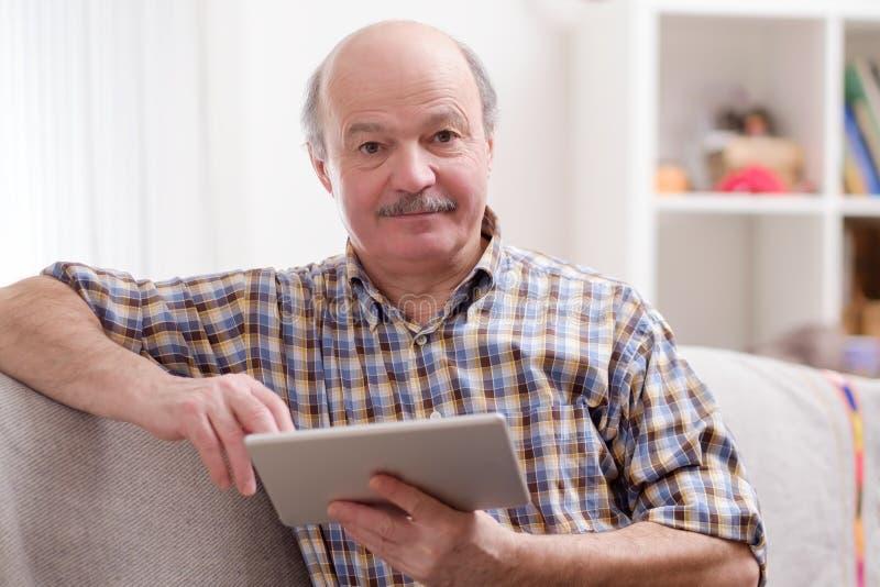 使用在家坐的片剂的老人 库存照片