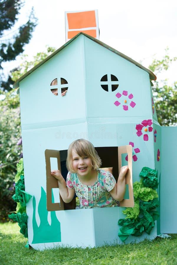 使用在家庭做的纸板议院里的两个孩子 库存图片