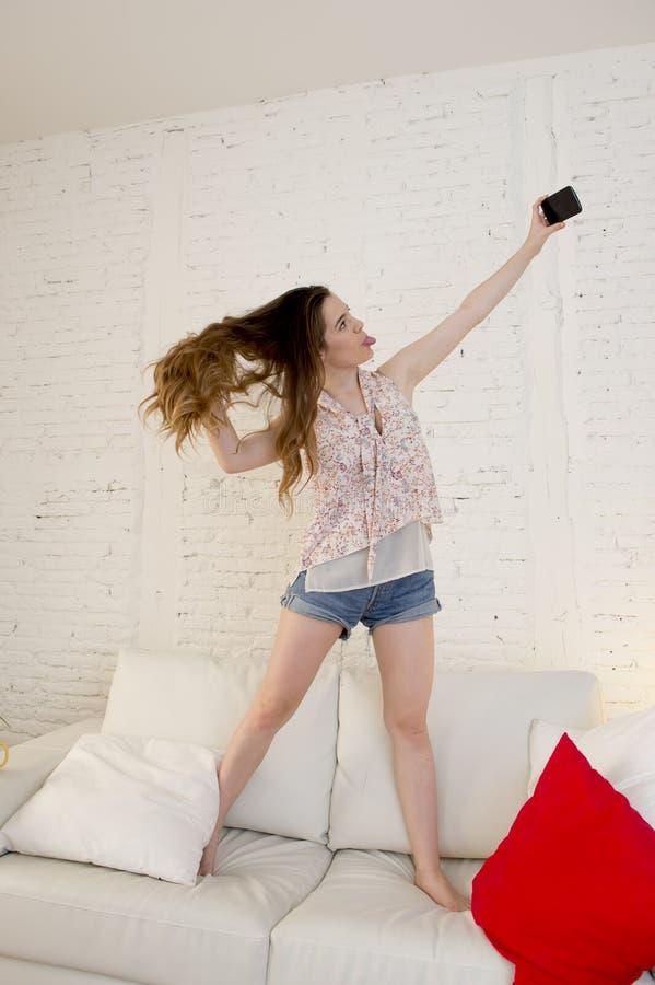 使用在家庭长沙发的愉快的可爱的女孩采取与获得的手机的selfie画象乐趣 免版税库存照片