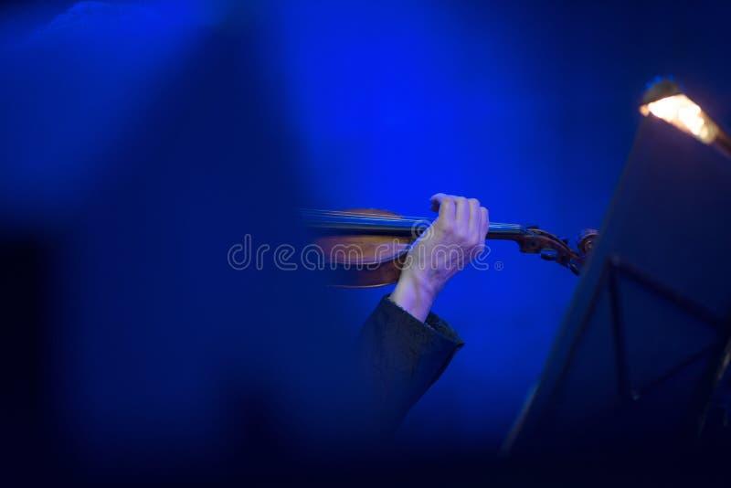 使用在小提琴的音乐家手 免版税库存照片