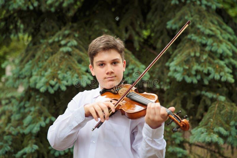 使用在小提琴的男孩 免版税库存照片