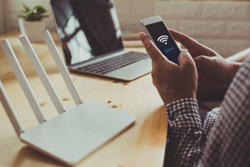 使用在居住的ro的wifi路由器和一个人的特写镜头智能手机 库存图片