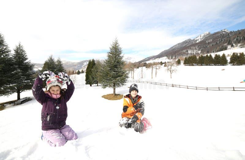 使用在山的雪的兄弟和姐妹在winte 免版税图库摄影