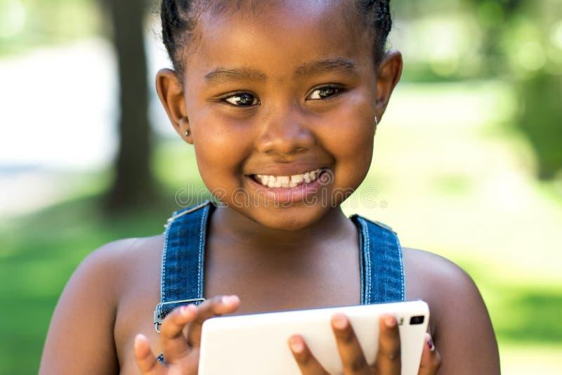 使用在巧妙的电话的逗人喜爱的非洲的女孩 免版税图库摄影