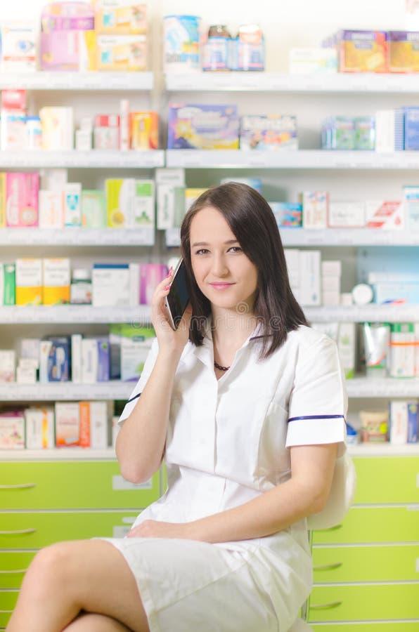 使用在巧妙的电话配药背景的年轻药剂师妇女app 药房 药片和医学 免版税图库摄影