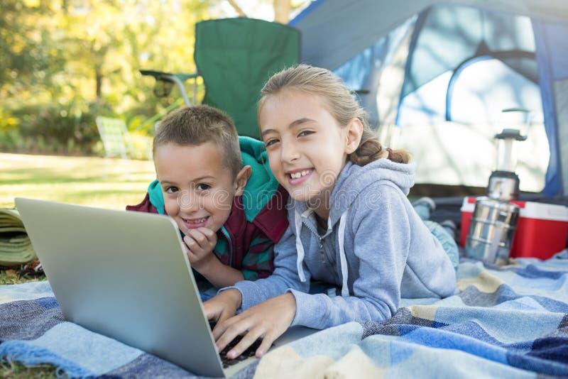 使用在帐篷之外的兄弟姐妹膝上型计算机在露营地 免版税库存照片