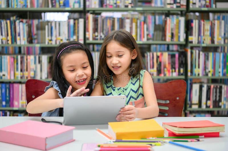 使用在平板电脑的两个一点愉快的逗人喜爱的女孩计算设备在图书馆里在学校 教育和自我学习技术 免版税库存图片