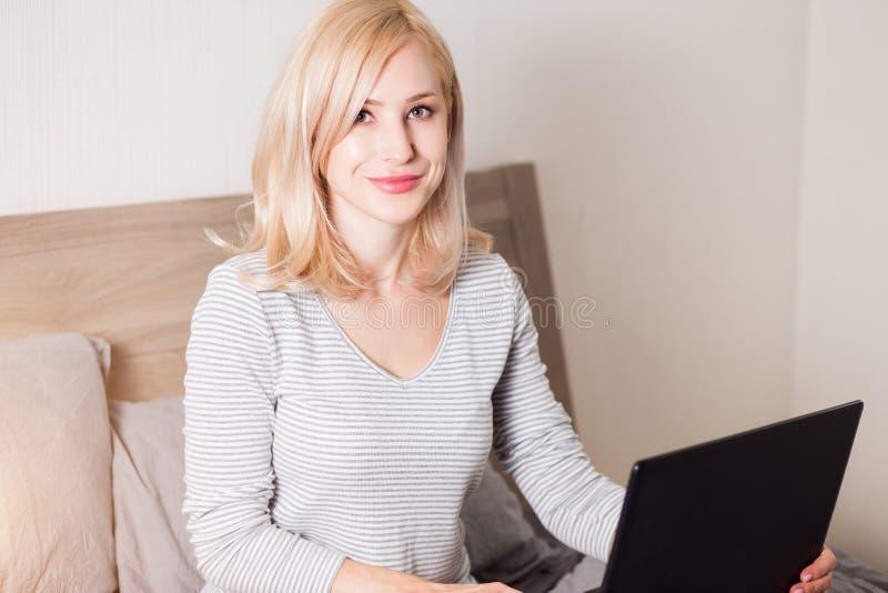 使用在床上的俏丽的妇女膝上型计算机 免版税库存照片