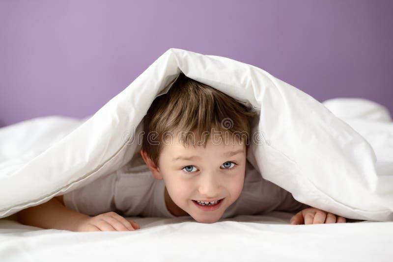 使用在床上的可爱的笑的男孩在一条白色毯子或床罩下 免版税库存照片