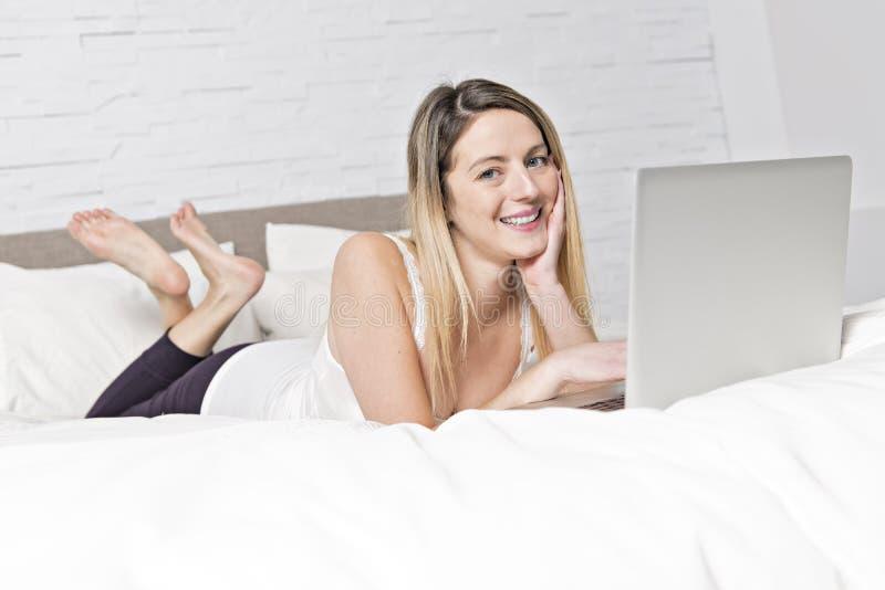 使用在床上的年轻女人膝上型计算机 库存图片