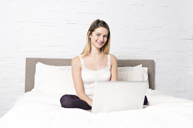 使用在床上的年轻女人膝上型计算机 免版税库存照片