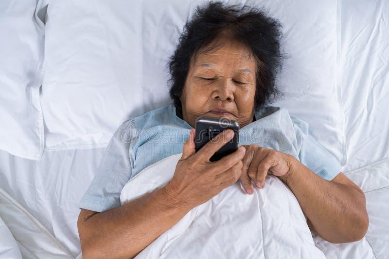 使用在床上的资深妇女手机 免版税图库摄影