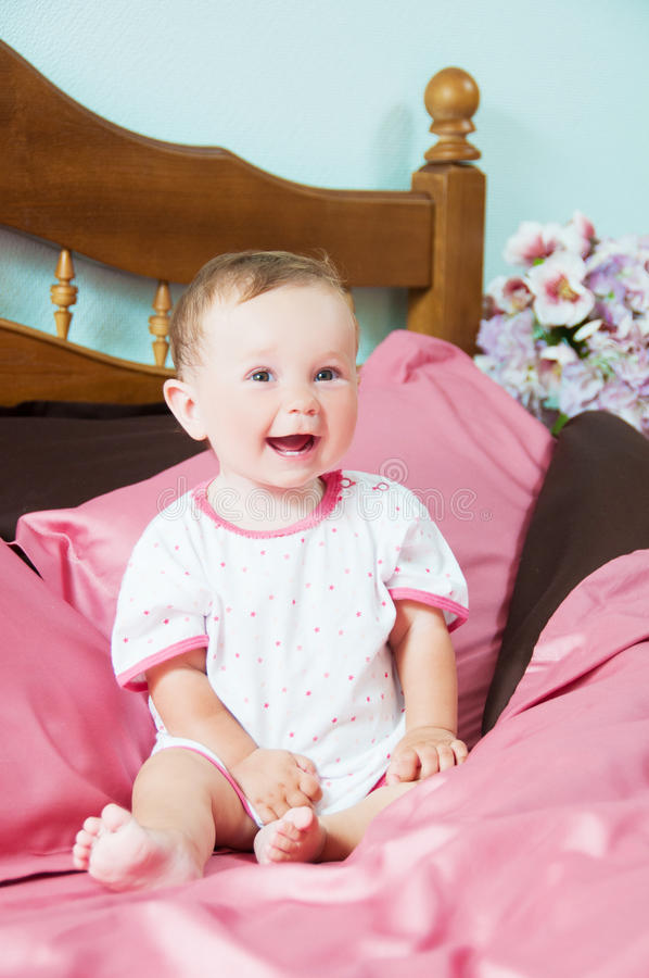 使用在床上的逗人喜爱的愉快的笑的婴孩 库存照片