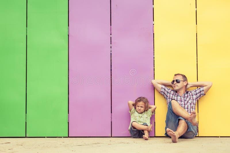使用在房子附近的父亲和儿子在天时间 免版税库存图片
