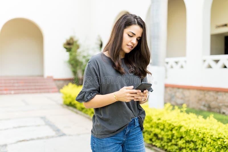 使用在手机的女性社会媒介在庭院 免版税库存照片