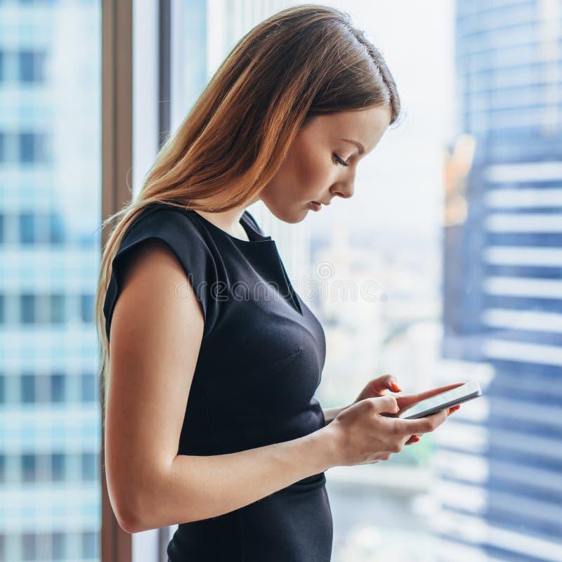 使用在手机的确信的年轻女性apps站立在大窗口附近在现代办公室 库存照片