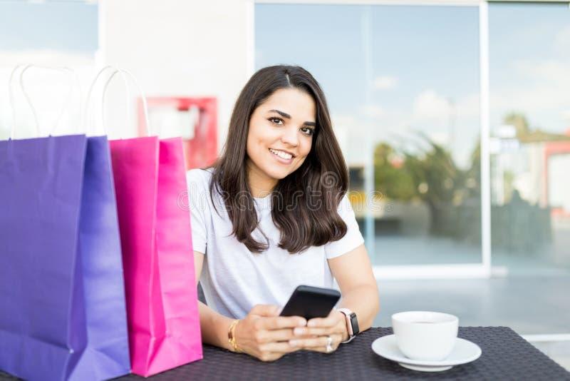 使用在手机的Shopaholic妇女社会媒介在咖啡馆 免版税图库摄影