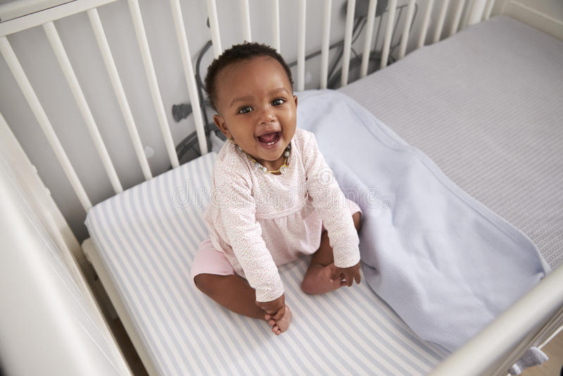 使用在托儿所轻便小床的愉快的女婴画象  免版税库存照片