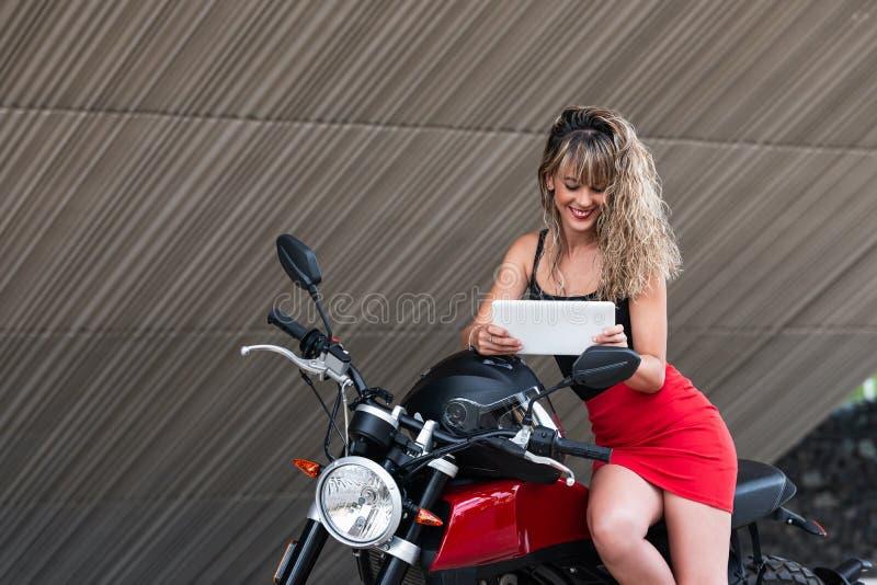使用在摩托车的美丽的年轻女人片剂 库存照片