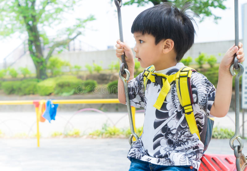 使用在操场摇摆的亚裔男孩 免版税图库摄影