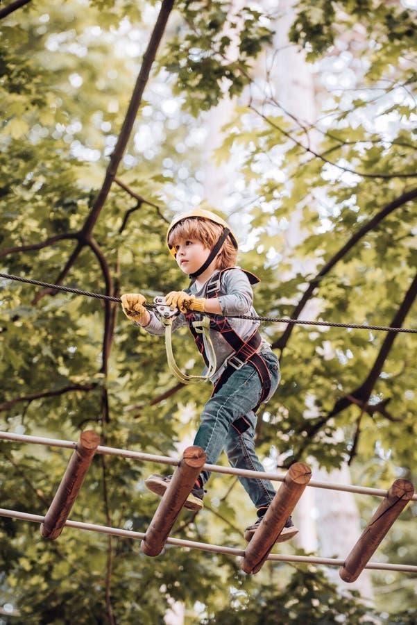 使用在操场的孩子 享受一好日子的逗人喜爱的小学生男孩在一个上升的冒险活动公园 ?? 库存图片