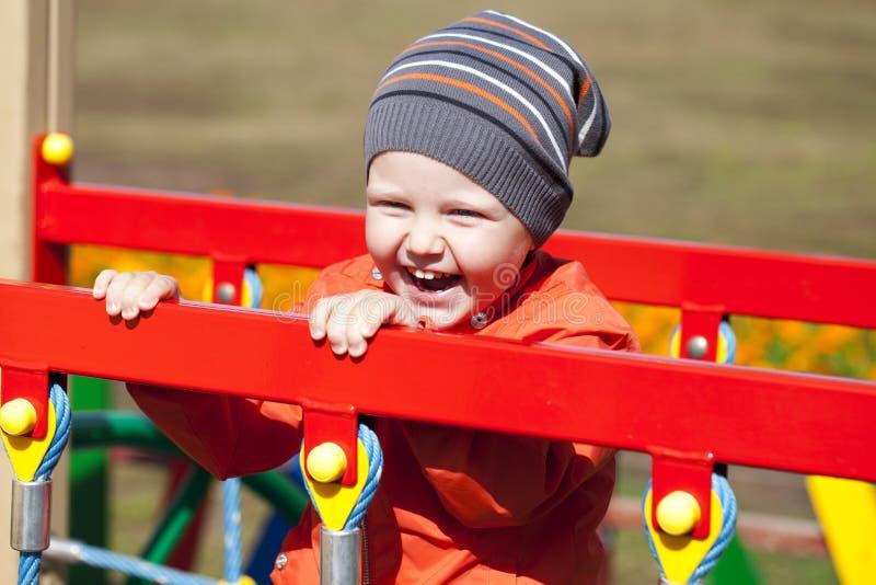 使用在操场的小男孩在秋天公园 免版税库存照片