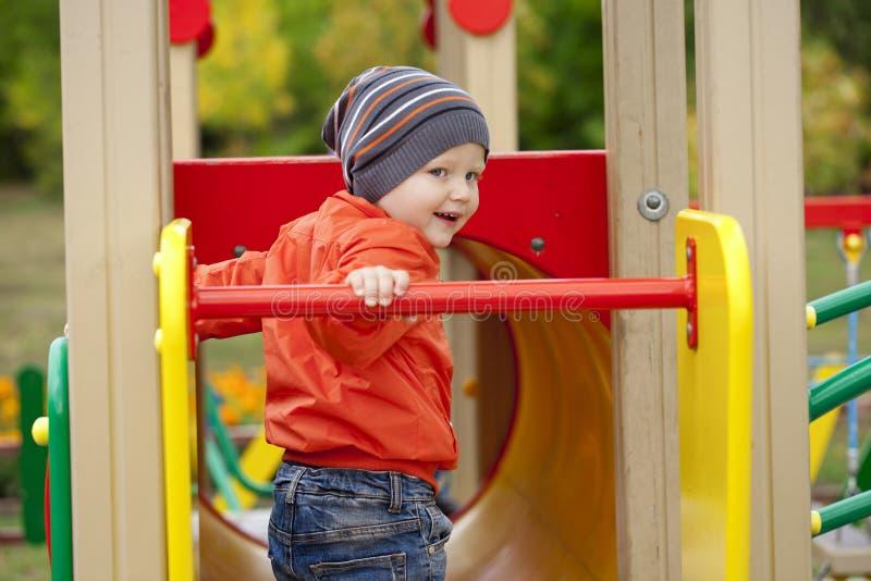 使用在操场的小男孩在秋天公园 免版税库存图片