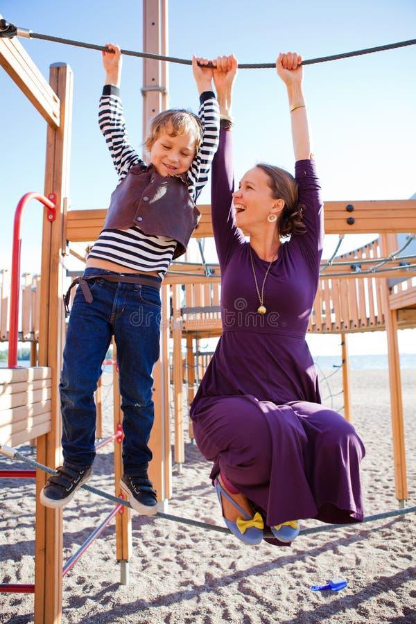 使用在操场的母亲和儿子。 免版税库存图片