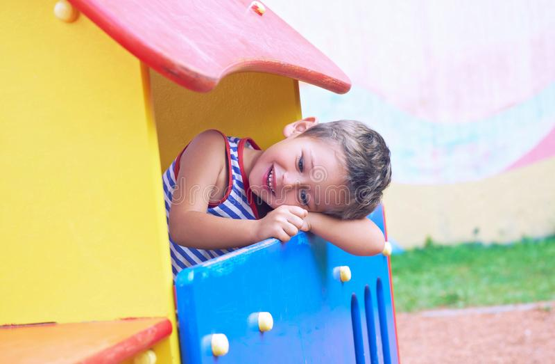 使用在操场的滑稽的逗人喜爱的愉快的小男孩 幸福、乐趣和喜悦的情感 免版税库存照片