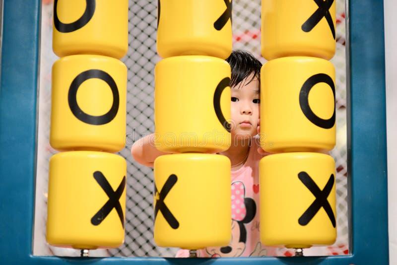 使用在操场的逗人喜爱的亚裔女孩室内 免版税图库摄影