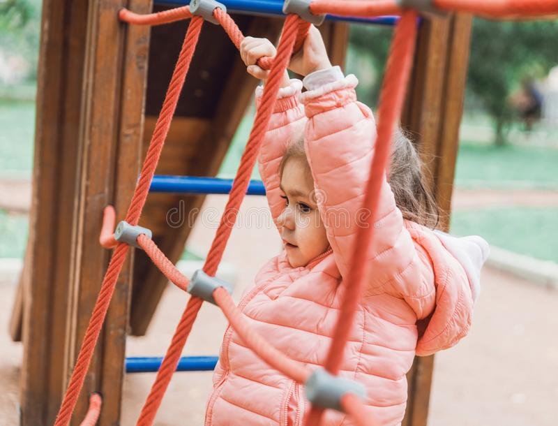 使用在操场的逗人喜爱的小女孩 库存照片