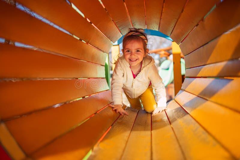 使用在操场的隧道的愉快的儿童女孩 免版税库存图片