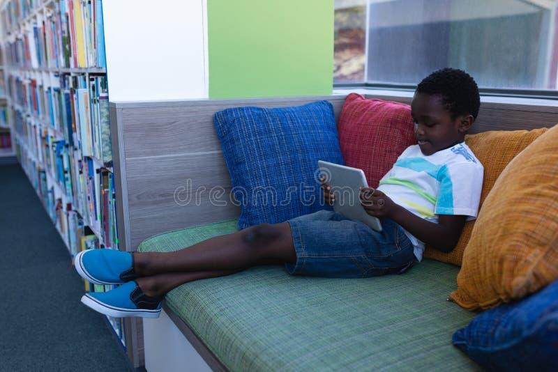 使用在数字片剂的男小学生,当坐长沙发在学校图书馆中时 免版税库存图片