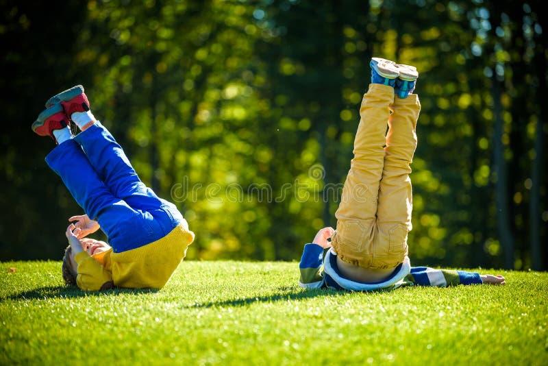 使用在新鲜的绿草草甸的两个愉快的男孩 跟斗和一起微笑兄弟孩子是最好的朋友 库存照片
