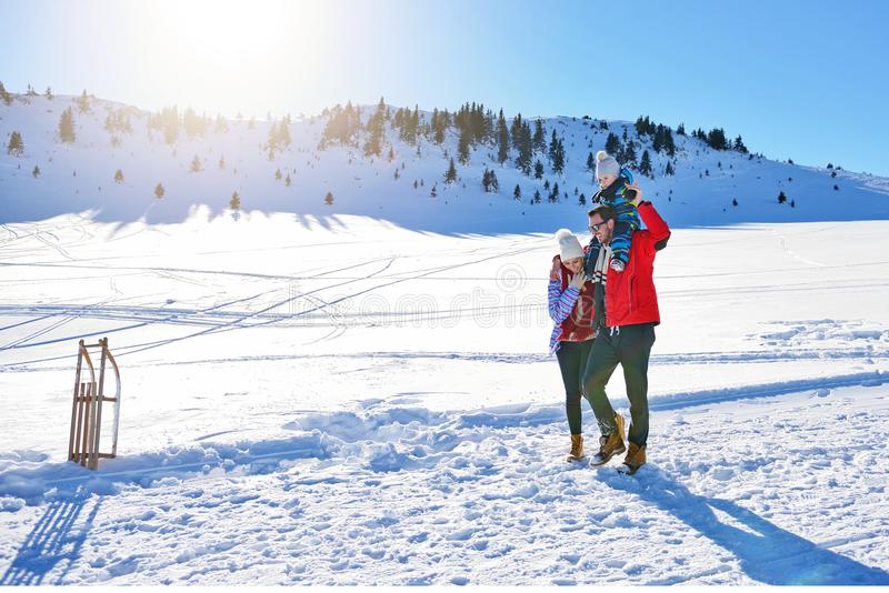 使用在新鲜的雪的愉快的年轻家庭室外美好的晴朗的冬日本质上 库存照片