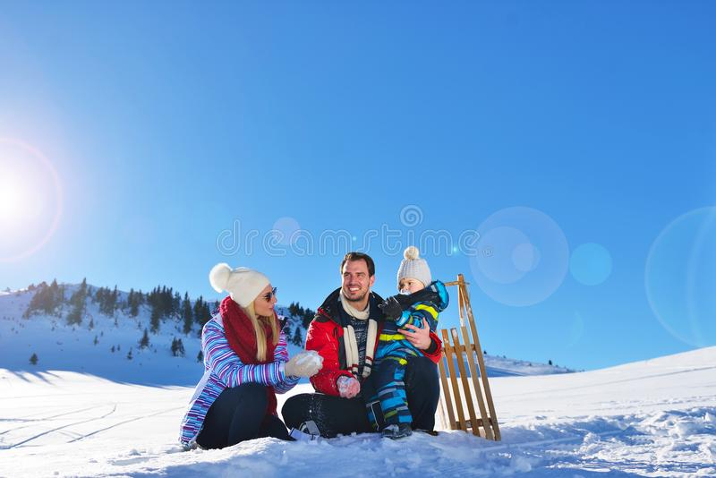 使用在新鲜的雪的愉快的年轻家庭室外美好的晴朗的冬日本质上 库存图片