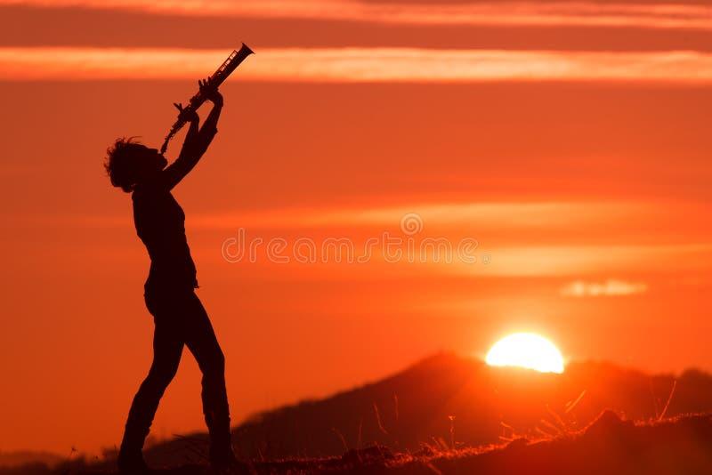 使用在日落的萨克斯管吹奏者 免版税图库摄影