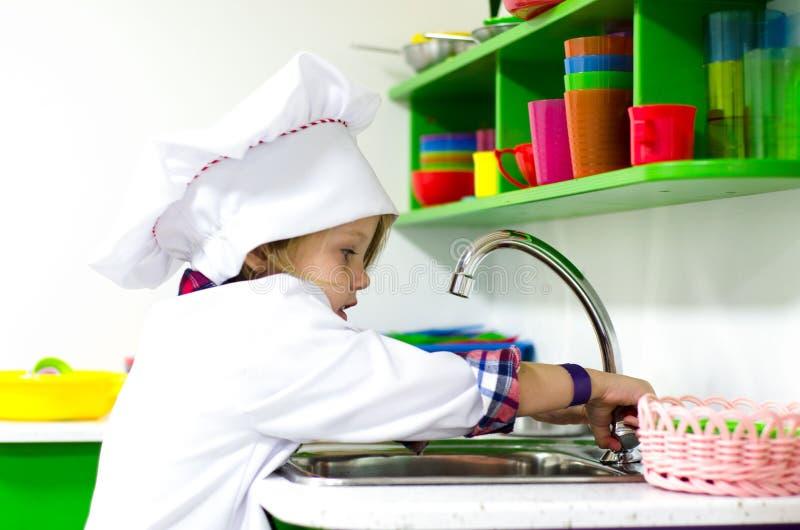 使用在明亮的厨房里的厨师帽子的小女孩 库存照片