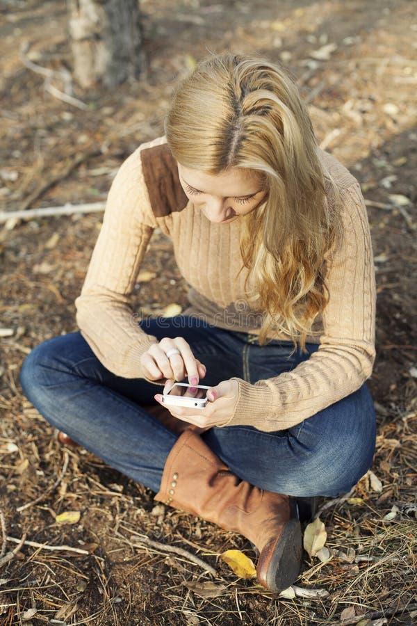 使用在智能手机的女孩互联网无线在natu 免版税库存图片