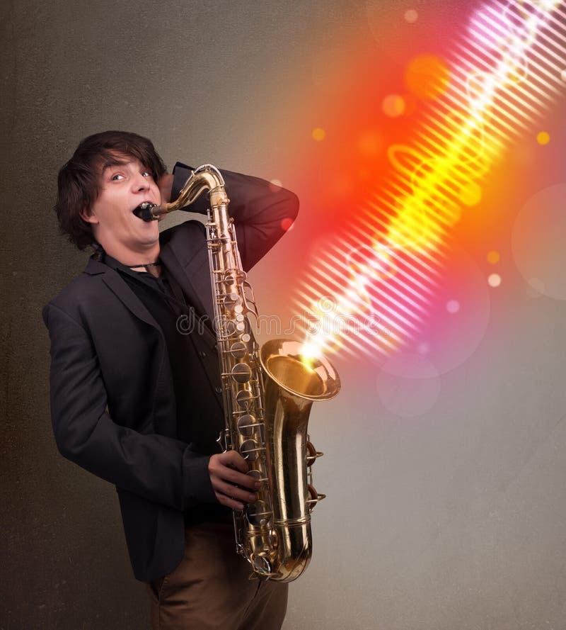 使用在有五颜六色的声波的萨克斯管的年轻人 库存照片