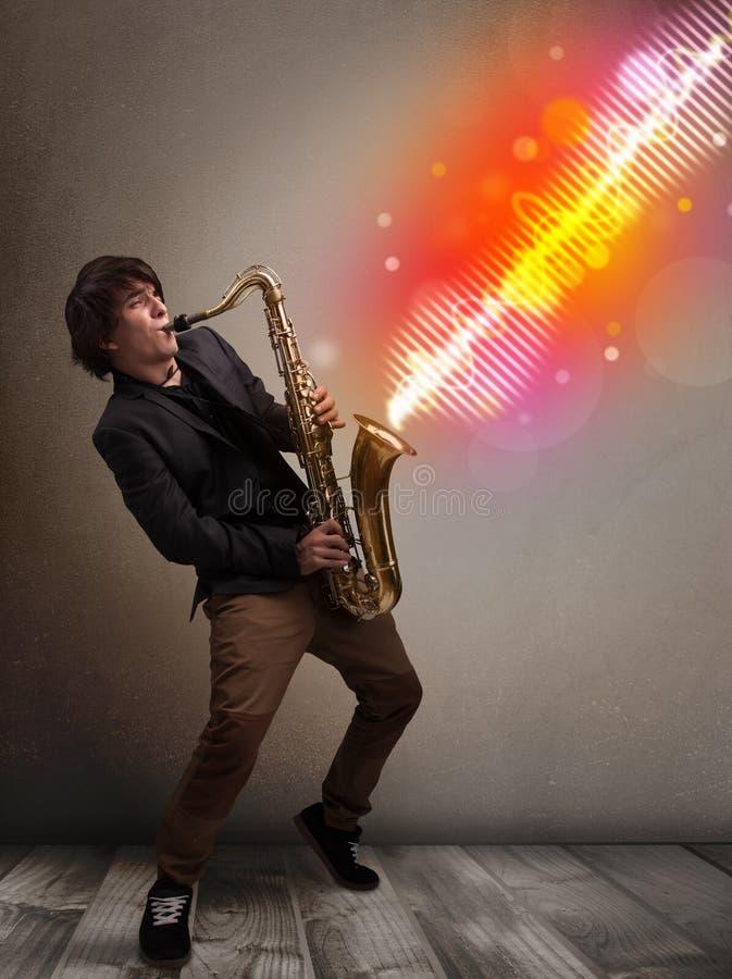使用在有五颜六色的声波的萨克斯管的年轻人 免版税库存照片