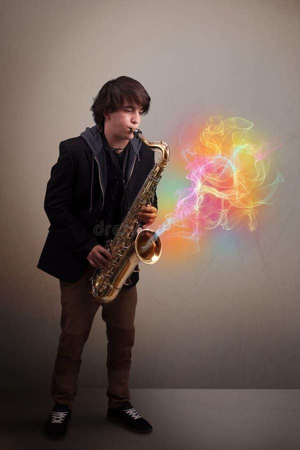 使用在有五颜六色的摘要的萨克斯管的可爱的音乐家 免版税图库摄影